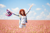 Cute woman in the field with flowers — Stock Photo