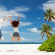Happy couple jumping on the tropical beach — Stock Photo