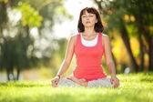 Jolie femme faire des exercices d'yoga dans le parc — Photo