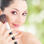 Ung kvinna med borste för makeup — Stockfoto