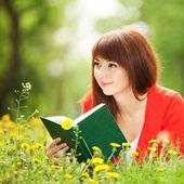 молодая женщина, читая книгу в парке с цветами — Стоковое фото
