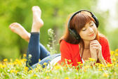 Happy woman with headphones relaxing in the park — Stock Photo
