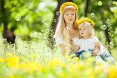 Szczęśliwa matka i córka dmuchanie baniek w parku — Zdjęcie stockowe