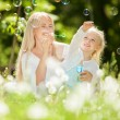 Happy mother and daughter blowing bubbles in the park — Stock Photo