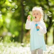 Cute little girl blowing bubbles in the park — Stock Photo