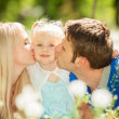 Happy mother and father kissing their daughter in the park — ストック写真