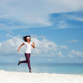 Young woman running on the beach — Stock Photo