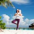 Pretty woman doing yoga exercises on the tropical beach — Stock Photo