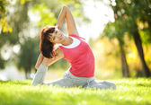Pretty woman doing yoga exercises in the park — Stockfoto