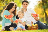 Happy family having a picnic in the green garden — Stok fotoğraf