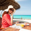 Fashion woman having breakfast on the beach — Stock Photo #31613473
