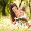 Foto de Stock  : Mother with daughter read book in park