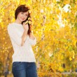 Stock Photo: Young pretty woman walking in the autumn park
