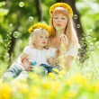 Happy mother and daughter blowing bubbles in park — Stock Photo #31618547