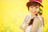 Cute woman in the field with flowers — Stockfoto