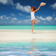 Happy young woman in white dress with hat jumping on the beach — Stock Photo
