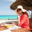 Fashion woman having breakfast on the beach — Stock Photo