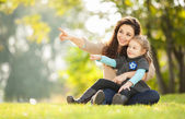 Happy woman and daughter showing to something in the park — Stock Photo