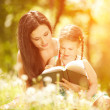 Mother with daughter read book in park — Stock Photo #34323375