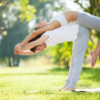 Couple Yoga, man and woman doing yoga exercises in the park — Stock Photo #34323961