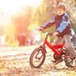 Happy boy with bicycle in the autumn park — Stock Photo