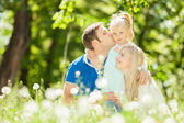 Happy mother, father and daughter in the park — Стоковое фото