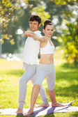 Couples Yoga, man and woman doing yoga exercises in the park — Stock fotografie