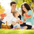 Happy family having a picnic in the autumn garden — Stock Photo