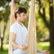 Anti-gravity Yoga, mdoing yogexercises in park — Stock Photo #34486867
