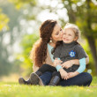 Mother kissing her daughter in the park — Stock Photo #34487011