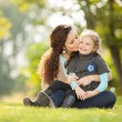 Stock Photo: Mother kissing her daughter in the park
