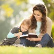Mother with daughter read a book in the park — Stock Photo
