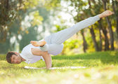 Man doing yoga exercises in the park — Foto de Stock