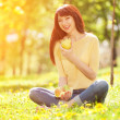 Happy woman eating fruits in the park — Stock Photo #34872251