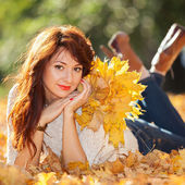 Young pretty woman relaxing in the autumn park — Stock Photo