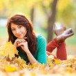 Stock Photo: Young pretty woman relaxing in the autumn park