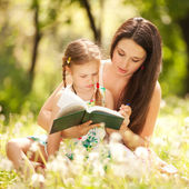 Mother with daughter read the book in the park — Stock Photo