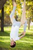 Anti-gravity Yoga, man doing yoga exercises in the park — Stock fotografie