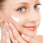 Cute woman applying cream to her face — Stock Photo