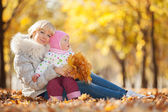 Mother and daughter in the autumn park — Stock Photo