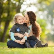 Mother kissing her daughter in the park — Stock Photo