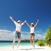 Happy couple jumping on the tropical beach — Stockfoto