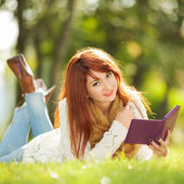 Young pretty woman with tablet in the park — Stock Photo