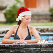 Beautiful woman with santa hat relaxing in jacuzzi at spa center — Stock Photo