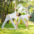 Couple Yoga, man and woman doing yoga exercises in the park — Stock Photo