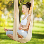 Anti-gravity Yoga, woman doing yoga exercises in the park — Stock Photo