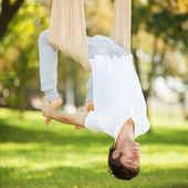 Anti-gravity Yoga, man doing yoga exercises in the park — Stock Photo