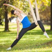 Anti-gravity Yoga, woman doing yoga exercises in the park — Stock Photo