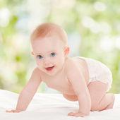 白いベッドの上の美しい青い目を持つかわいい赤ちゃん — ストック写真