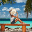 Fashion woman siting on a bench at the beach — Stock Photo
